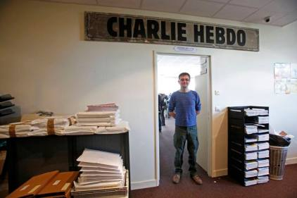 File photo of French cartoonist Charb, publishing director of French satirical weekly Charlie Hebdo, posing for photographs at their offices in Paris